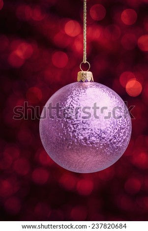 Christmas ball against red defocused lights background - stock photo
