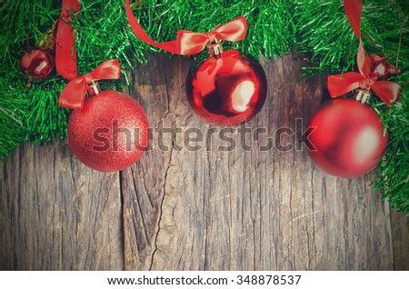 Christmas ball and green tinsel on wooden table