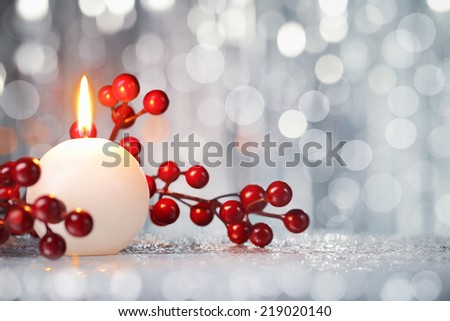 Christmas ball and lights hanging on fence at snowy night - stock photo