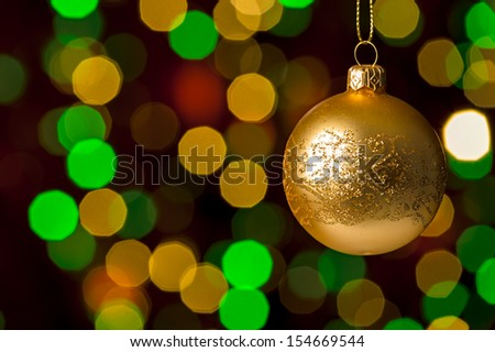 Christmas ball hanging defocused sparkling lights on the background - stock photo