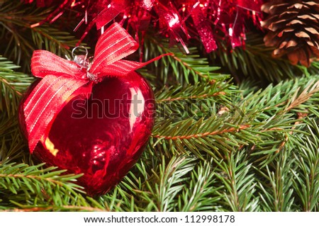 Christmas ball (heart) on tinsel background - stock photo