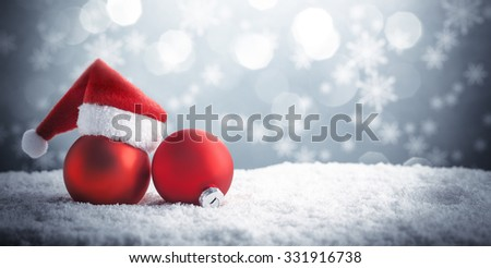 Christmas ball in the hat of Santa Claus on snow. - stock photo