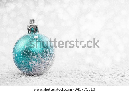 Christmas ball in the snow on blurred light background. A holiday card. Traditional Christmas decorations. - stock photo