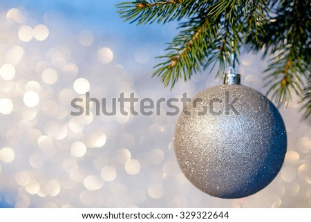 Christmas ball on a Christmas tree branch over blurred shiny background. Space for text.