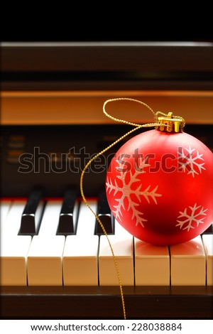 Christmas ball on piano keys - stock photo