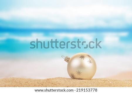 Christmas ball on yellow sand and sea background - stock photo