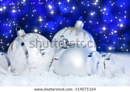 christmas ball ornament and ribbon in snow before blue bokeh background