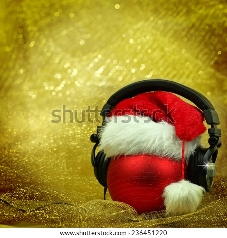 Christmas ball with headphones in glittering background - stock photo
