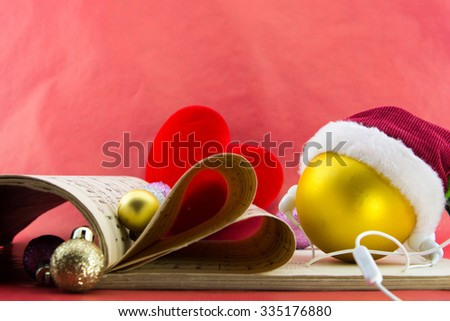Christmas ball with Santa's hat and earphones, music notation book with pages shaping heart, on red background. - stock photo