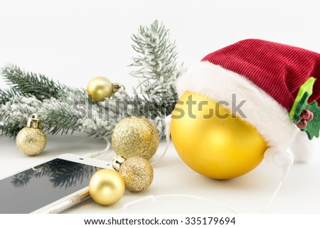 Christmas ball with Santa's hat and smartphone with earphones, isolated on white with copy-space - stock photo