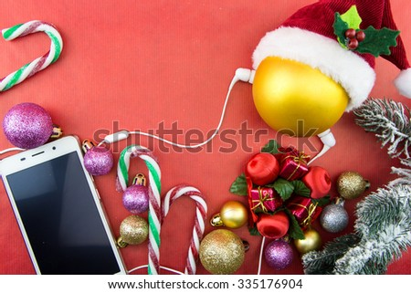 Christmas ball with Santa's hat and smartphone with earphones, on red with copy-space - stock photo