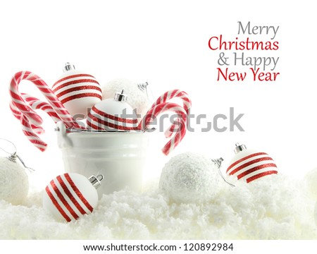 Christmas balls and candies in a cup on snow - stock photo