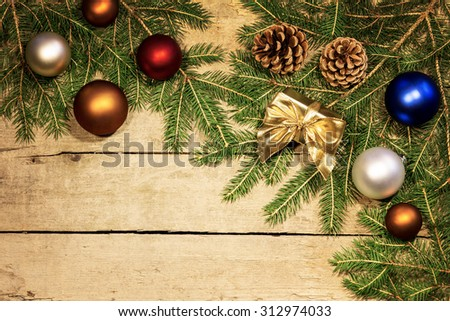 christmas balls and fir cones and branches on a wooden background