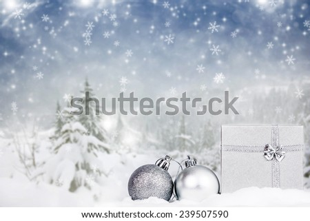 Christmas balls and gift box in the snow, snowy pine trees in the background - stock photo