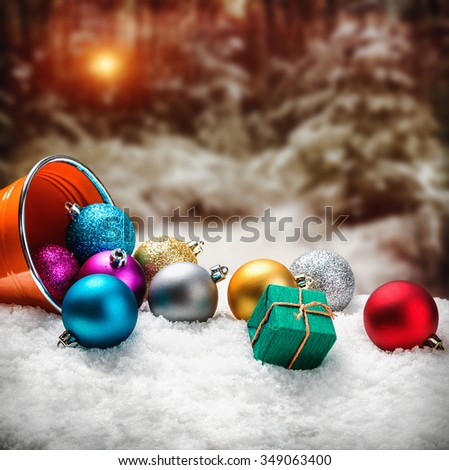 Christmas balls and gifts in the snow against the backdrop of the winter forest - stock photo