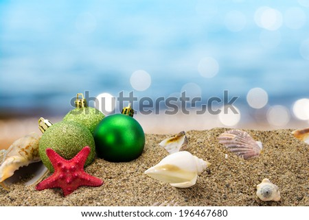 Christmas balls and shells on sand with summer sea background  - stock photo