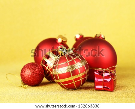 Christmas balls and small gift on yellow background