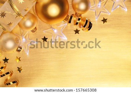 Christmas balls and star lights on golden background