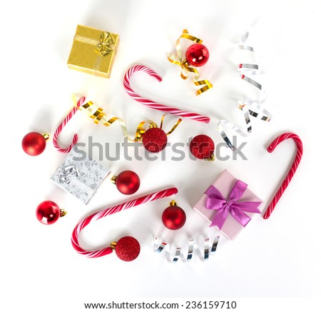 christmas balls, bright bows, golden and silver gift boxes and candy-cane on white surface, top view - stock photo