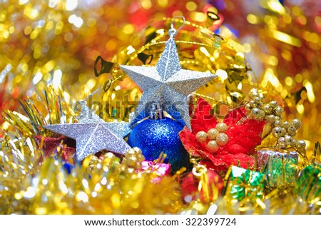 Christmas balls,five-pointed star,Christmas flower with box in the golden tinsel defocused backgrounds