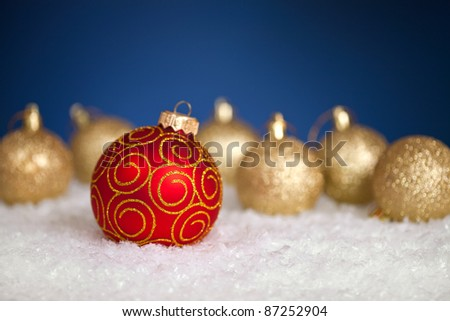 "Christmas balls in snow on blue background. ""Be different"" concept. Shallow depth of field"