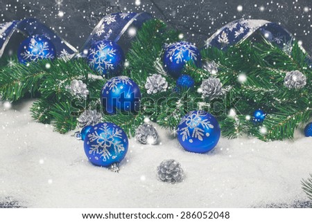 Christmas balls in snowfall, Christmas background.. Blue Christmas decorations and silver pine cones background. Done with a vintage retro filter. Macro, selective focus  - stock photo