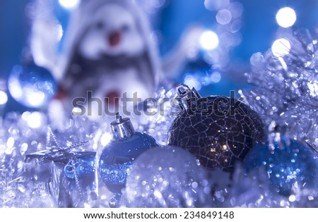 Christmas balls in tinsel and the background blur smile snowman - stock photo