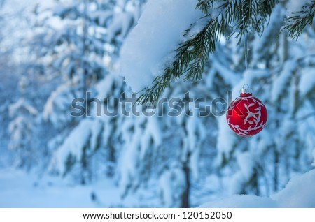 Christmas balls on a branch in a snowy forest - stock photo