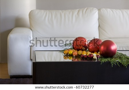 christmas balls on coffee table by white sofa in modern living room - stock photo