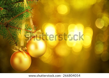 Christmas balls on fir tree on festive shiny background - stock photo