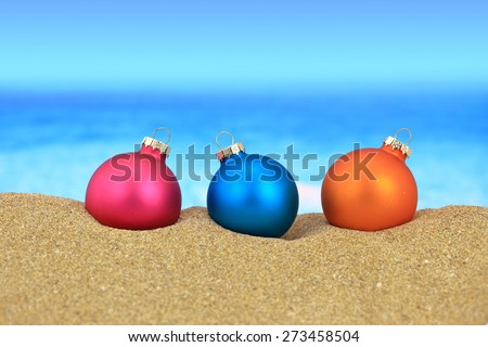Christmas balls on sandy beach - stock photo