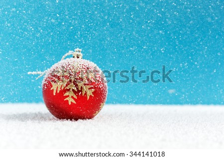 Christmas balls on snow, falling snow - stock photo