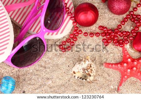 Christmas balls,seashells andh beach accessories on sand, close-up - stock photo