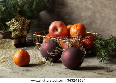 Christmas balls with mandarin oranges and apples on the table - stock photo