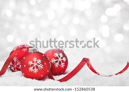 Christmas balls with ribbon on snow - stock photo