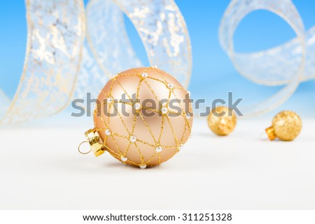 Christmas balls with ribbon on snow, on blue background - stock photo