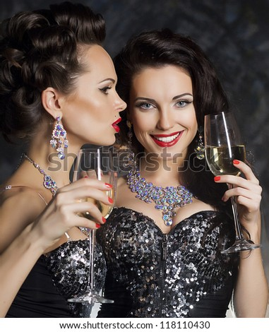 Christmas. Banquet. Two Happy Festive Young Fashion Women with Wine Glasses of Champagne Toasting - New Year - stock photo