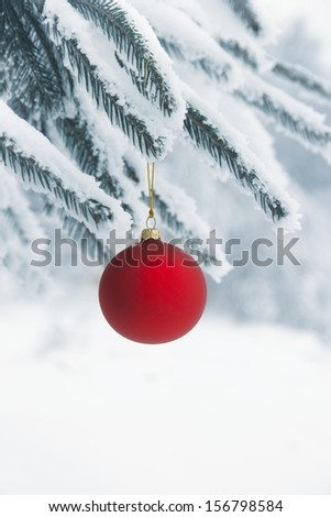christmas bauble hanging on a snowy tree - stock photo