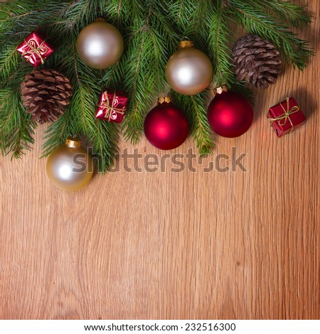 Christmas bauble on Christmas tree on wooden background.