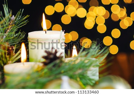 Christmas baubles and candle on black background of defocused golden lights. - stock photo