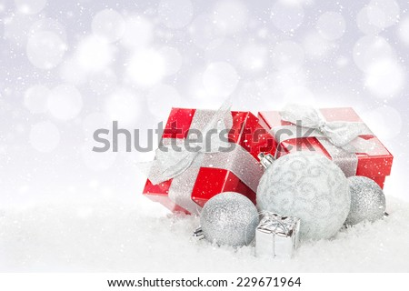 Christmas baubles and red gift boxes over snow bokeh background with copy space - stock photo