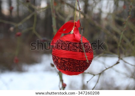 Christmas baubles hang from roses branches. - stock photo