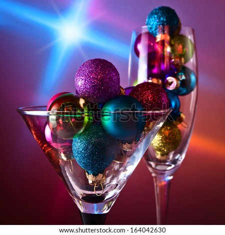 christmas baubles in wineglasses on  dark background. - stock photo