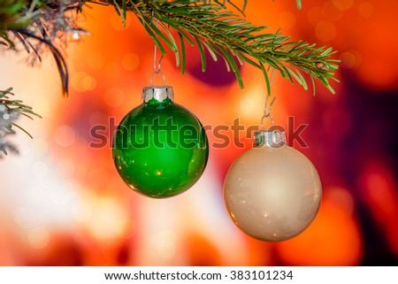 Christmas baubles on a pine branch by a fireplace - stock photo