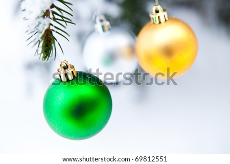 Christmas baubles on a snowy pine on a cold winter day
