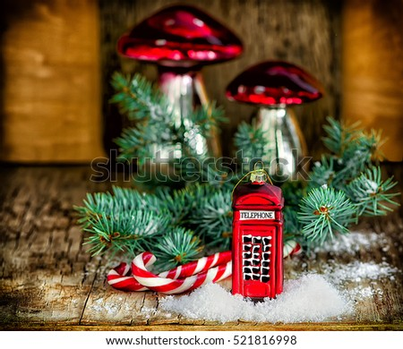 Christmas baubles Phone booth, mushrooms, candy cane Santa sticks and fir branch on the vintage wooden table. Christmas and New Year composition.
