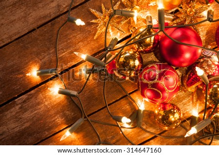 christmas baubles scattered on a wooden table wrapped in fairy lights - stock photo