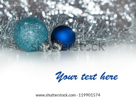 Christmas baubles with silver tinsel and silver bokeh background, with copy space - stock photo