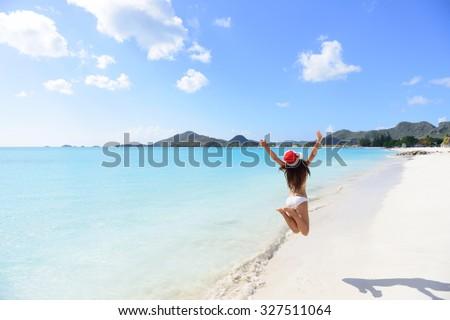 Christmas beach travel vacation woman in Santa hat jumping of joy on tropical Caribbean winter holidays getaway. Beautiful girl in bikini having fun under the sun traveling. - stock photo