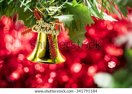 Christmas bell ornament hang on Christmas tree branch with red bokeh background - stock photo